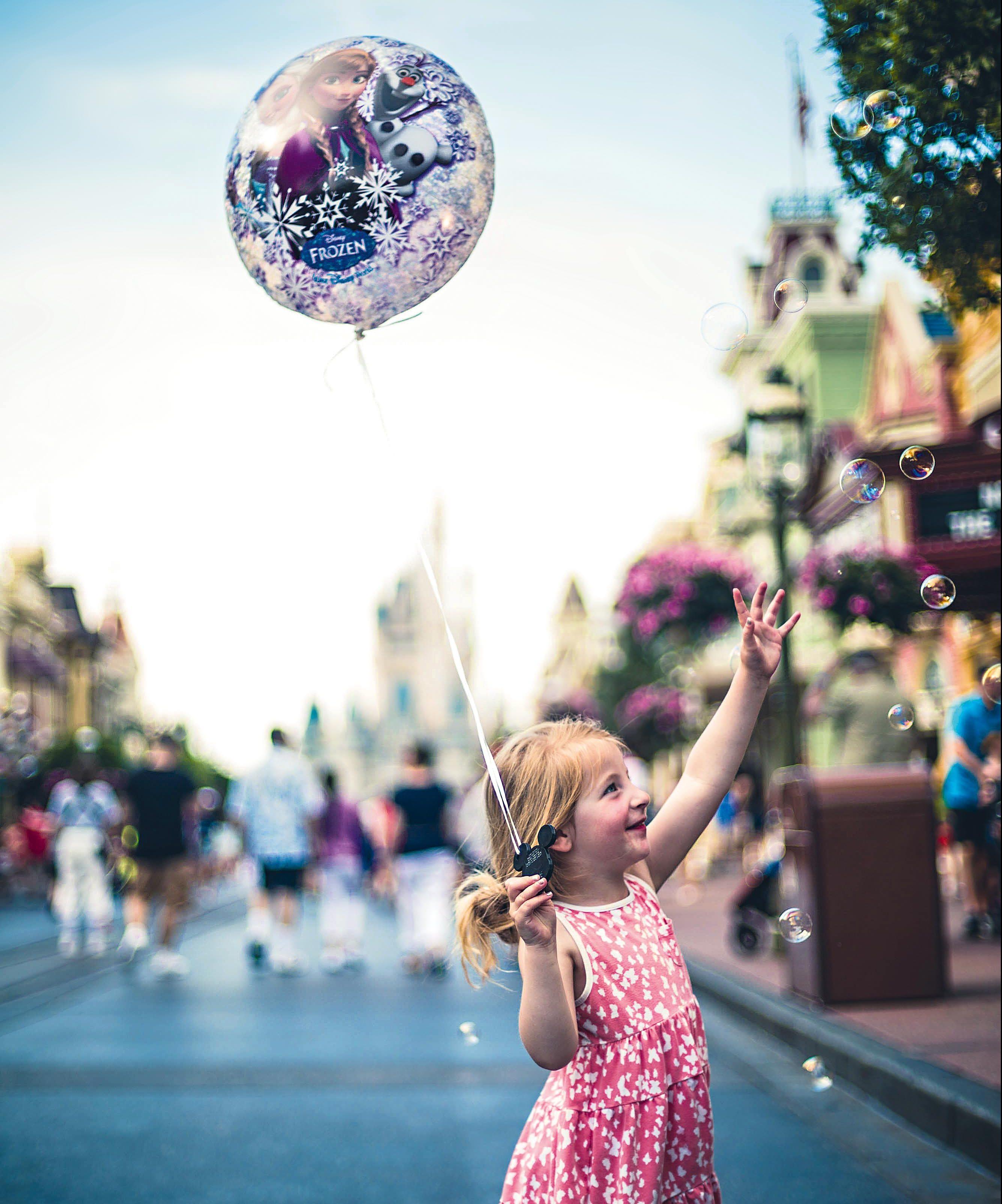 """Menina segura um balão com uma imagem do filme """"Frozen"""", enquanto tenta agarrar bolhas de sabão"""