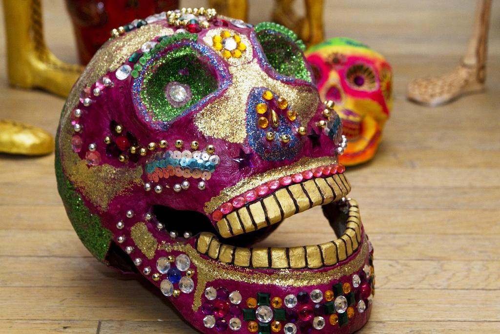 Caveira artesanal coberta em tintura, lantejoulas e brilhos, formando a tradicional pintura do Día de los Muertos