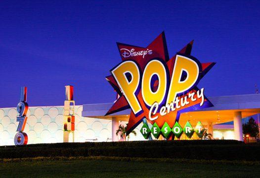 """A entrada de um prédio com formato futurístico, onde há um logo no estilo """"pop art"""" com o nome do resort"""
