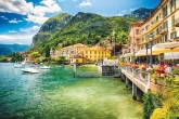 Do lado direito, um restaurante charmoso e à beira d'água é decorado com flores. Ao fundo, casarões amarelos. À esquerda, lanchas estão ancoradas no Lago Como