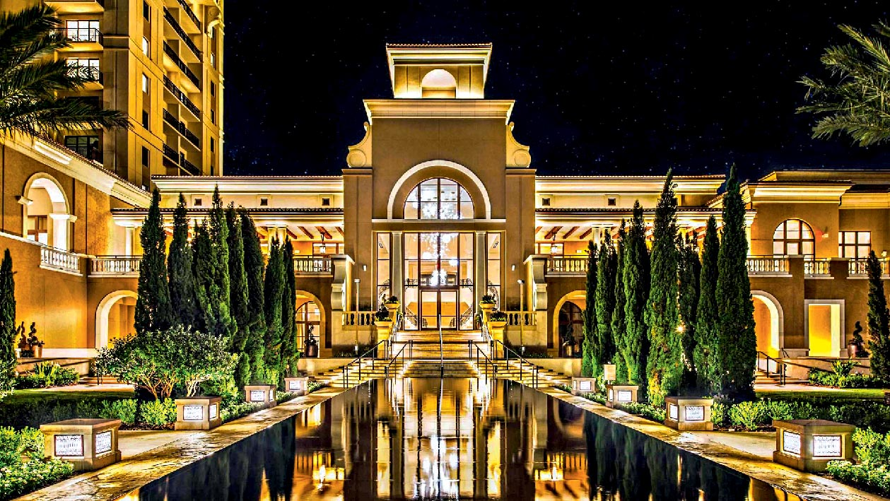 Uma grande piscina reflete a iluminação de um prédio luxuoso, que abriga o Four Seasons Orlando