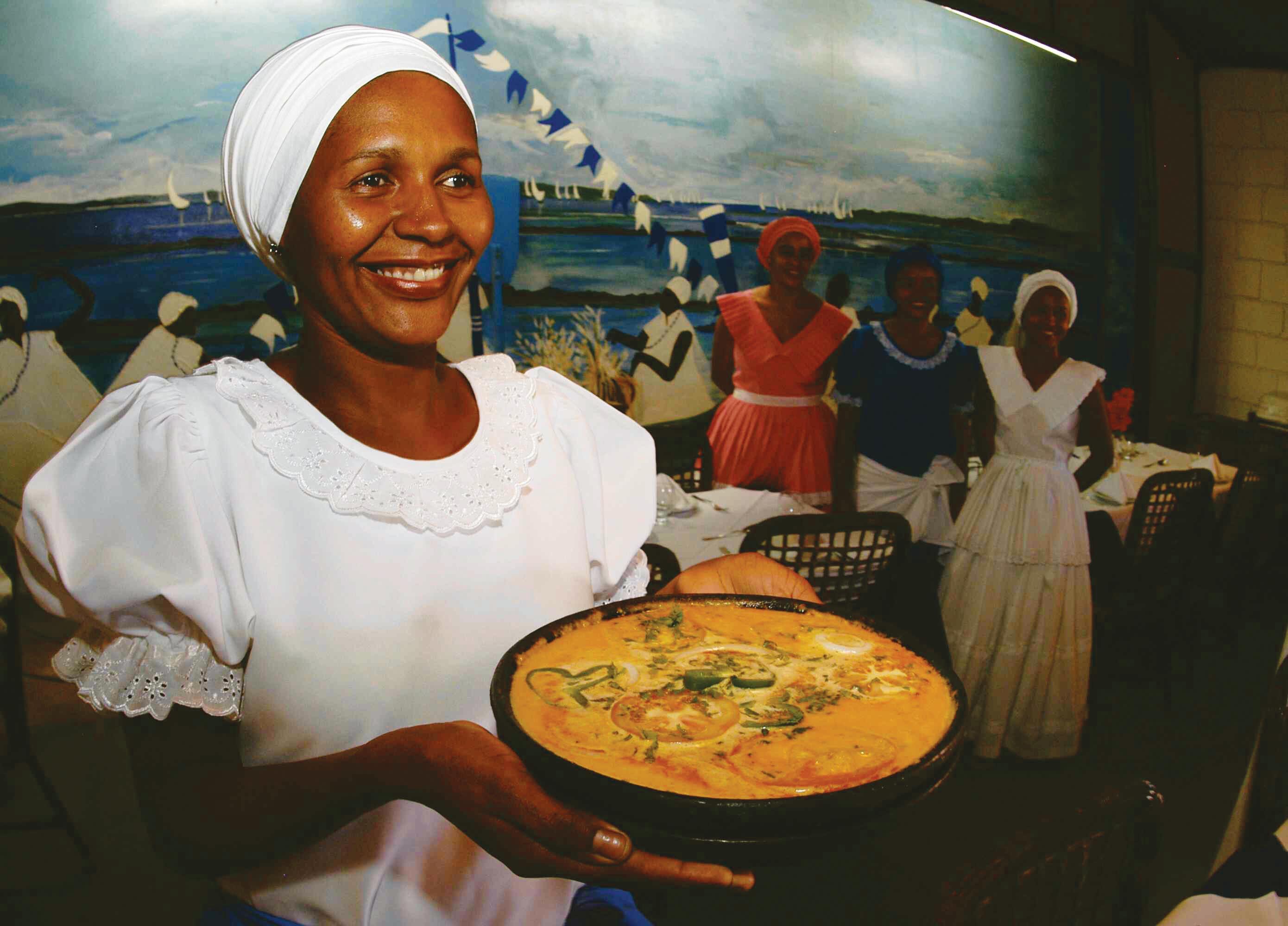 Mulher vestida de baiana, com um grande sorriso no rosto, oferecendo uma panela de barro com uma moqueca