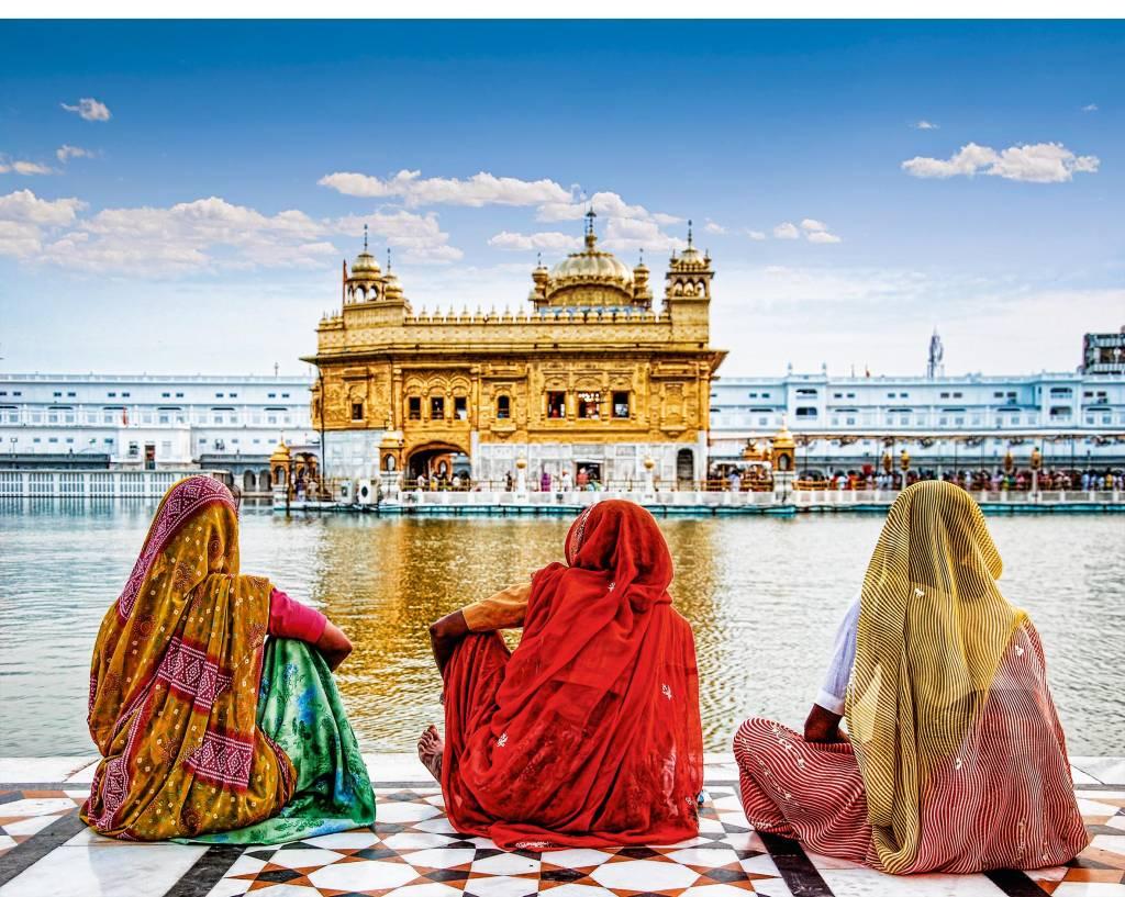 Três mulheres vestidas em sáris sentam-se à beira do rio, observando a movimentação na outra margem, em volta do Templo Dourado.