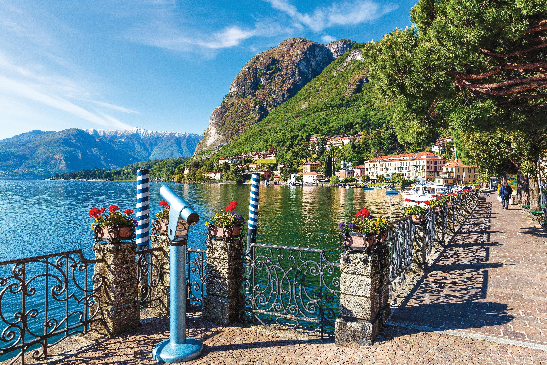 Uma luneta que aponta para o horizonte do Lago Como decora o canto de uma calçada de pedras, que é ladeada por árvores e com uma grade repleta de florzinhas