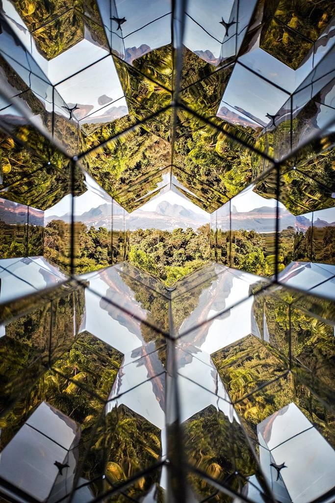 A vista da paisagem de Inhotim - árvores e céu ensolarado - por meio de uma espécie de caleidoscópio gigante de vidro, que reflete a vista diversas vezes