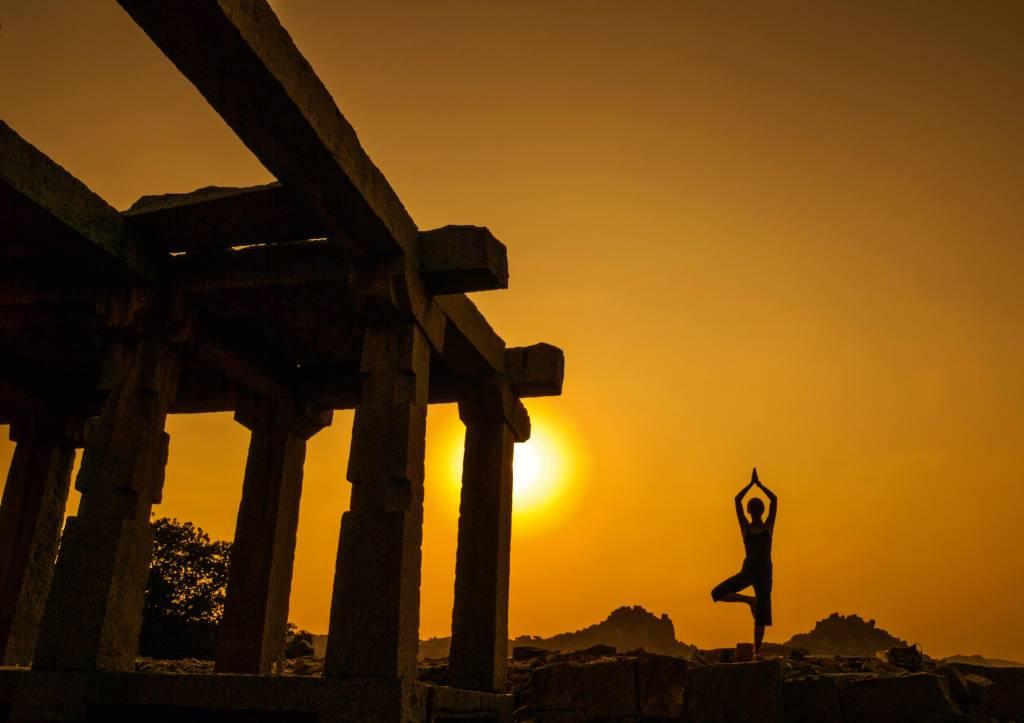 Mulher faz pose de ioga ao lado de uma construção aparentemente abandonada. Ela está contra o pôr-do-sol, de forma que suas feições não estejam visíveis