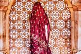 Mulher vestida em um sári se posiciona de frente a uma janela, cuja abertura está divida em furos formados por várias mandalas esculpidas