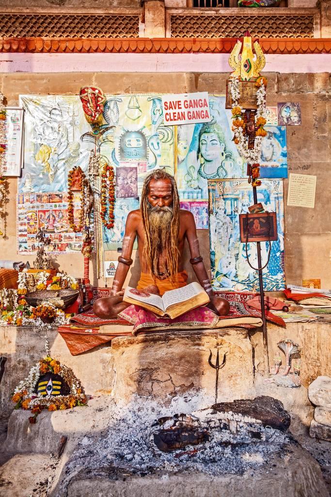 Sadhu está sentado em meio a múltiplos pôsteres e lembrancinhas, lendo um livro em pose de disciplina