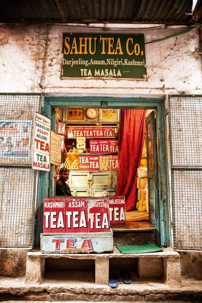 """Uma loja simplória de chá, de portas abertas, com grandes caixas de diferentes sabores de chá, todas elas com a palavra """"TEA"""" escrita em letras garrafais"""