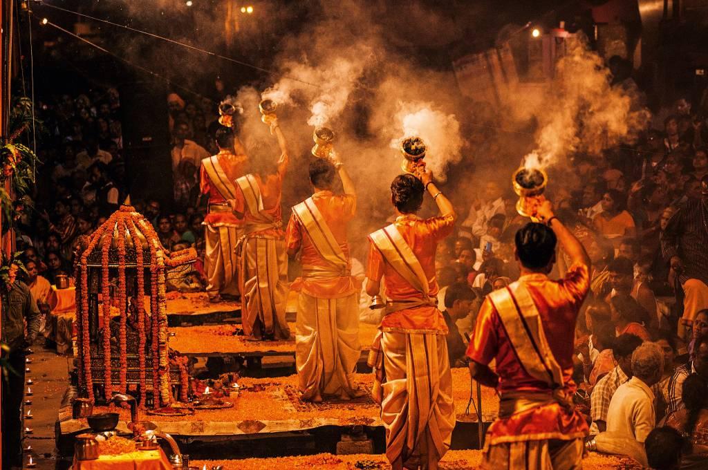 Pessoas em vestes cerimoniais realizam ritos em frente a uma multidão, em um ghat na beira do Ganges