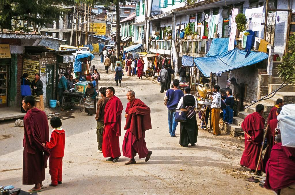 Pedestres e monges circulam por uma rua de terra, com alguma tendas de comércio instaladas esparsamente