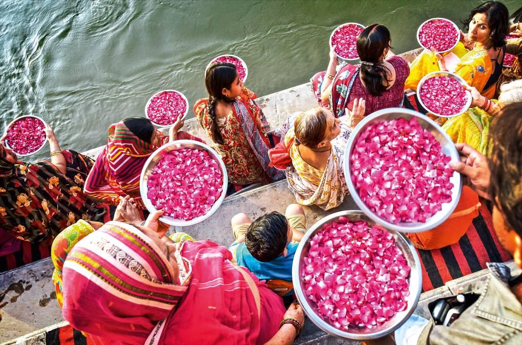 Em degraus de pedra localizados na margem do Ganges, miulheres se reúnem com bacias de pétalas de flores para jogá-las no rio, em oferenda