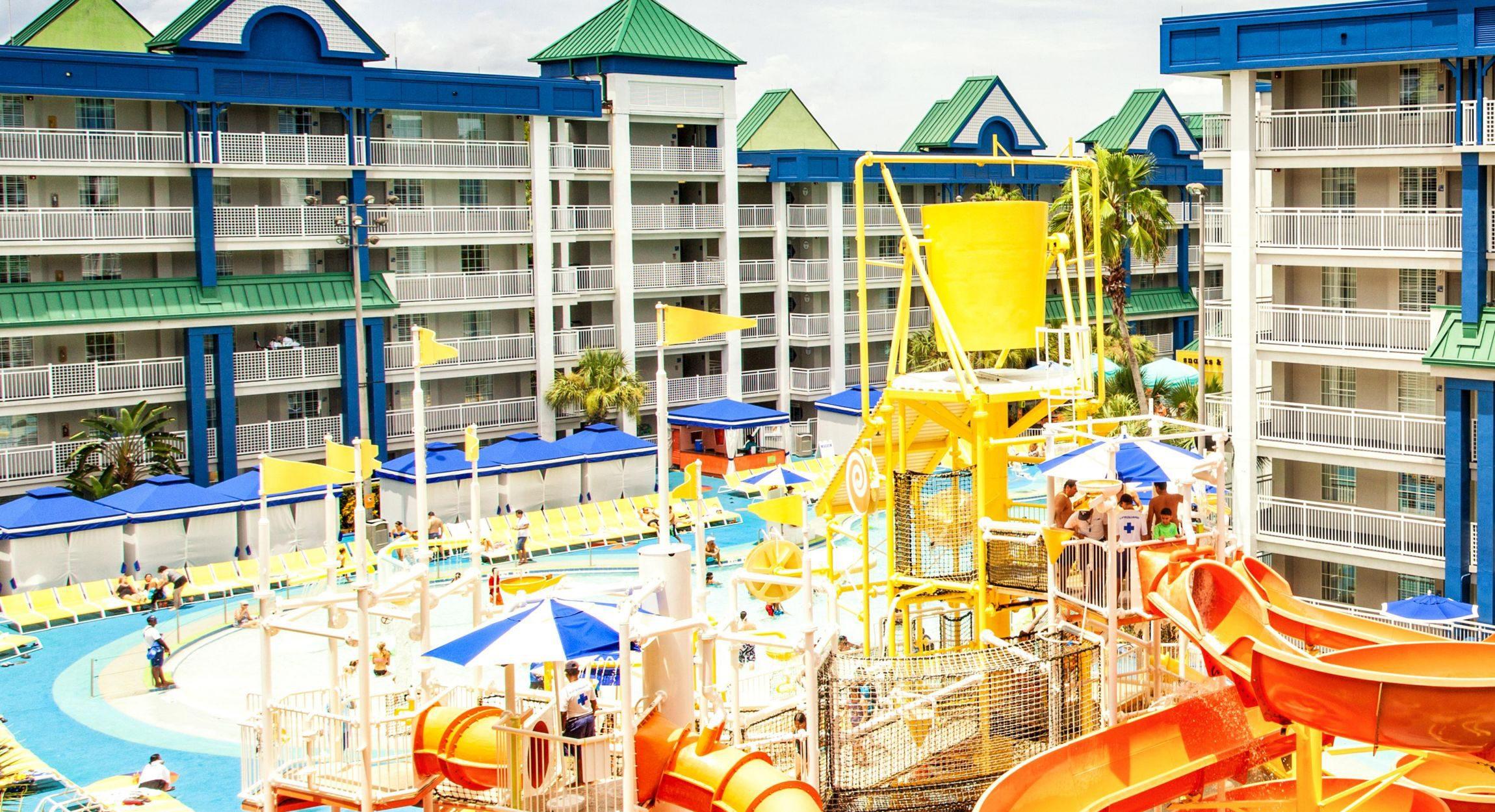 Um pequeno parque aquático, com crianças descendo escorregadores e em piscinas. Ao fundo, prédios com as varandas e os quartos dos hóspedes