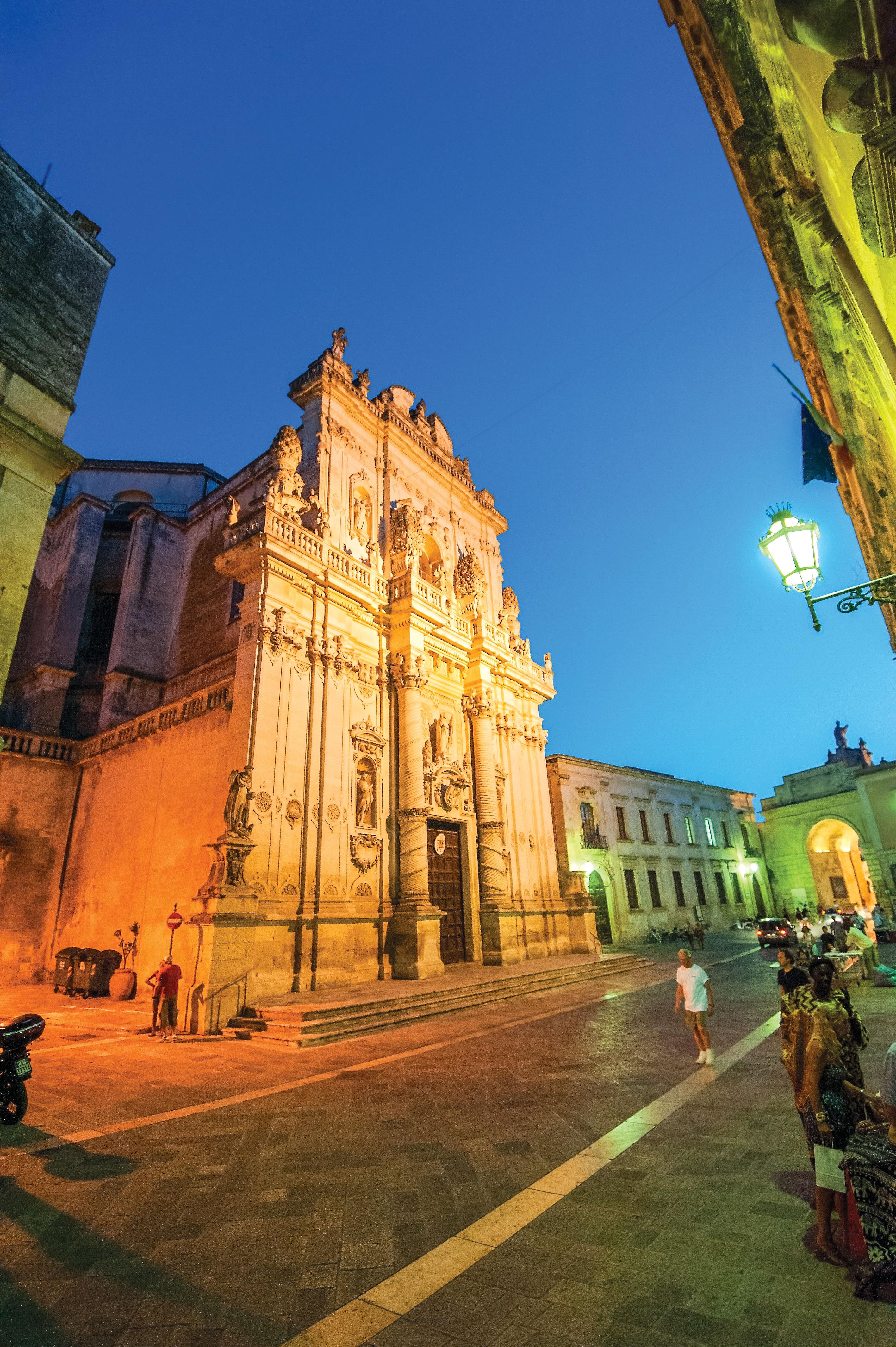 Igreja em estilo barroco iluminada com luzes, no cair da noite em Lecce