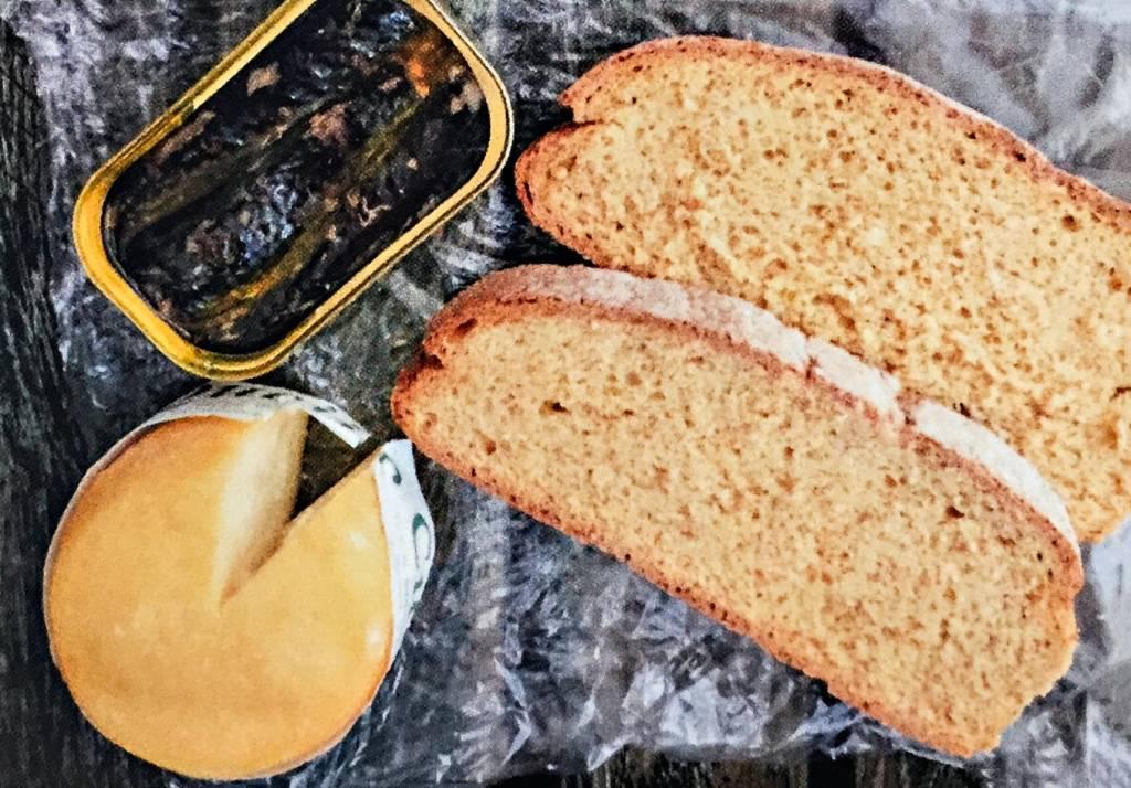 Duas fatias de pão, uma lata de sardinhas e uma roda de queijo do tamanho da lata, sobre um fundo de papel plástico