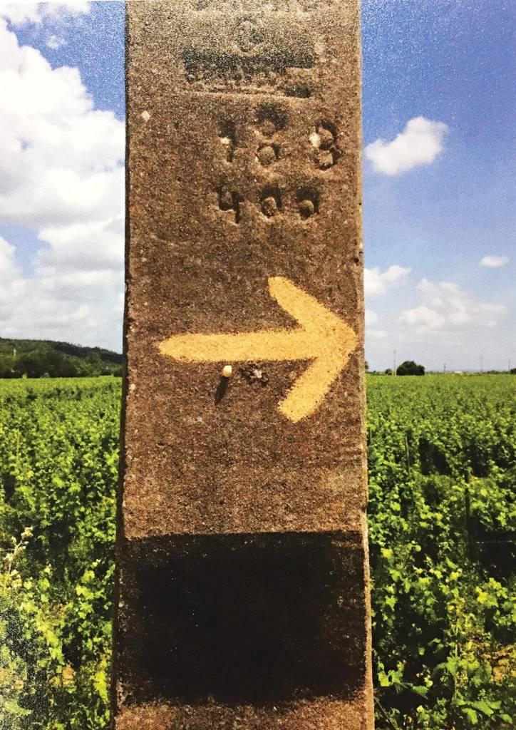 Um poste de pedra marcado à mão com uma seta, que indica o caminho