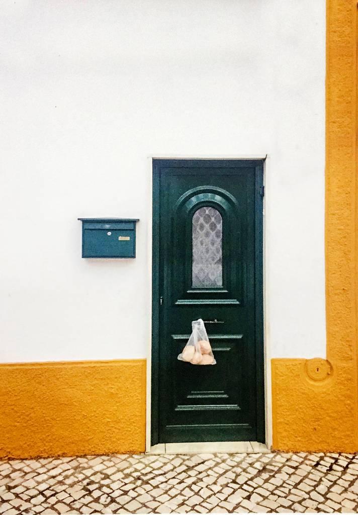 Uma porta solitária em uma parede tem um saco de quatro pães pendurado nela.