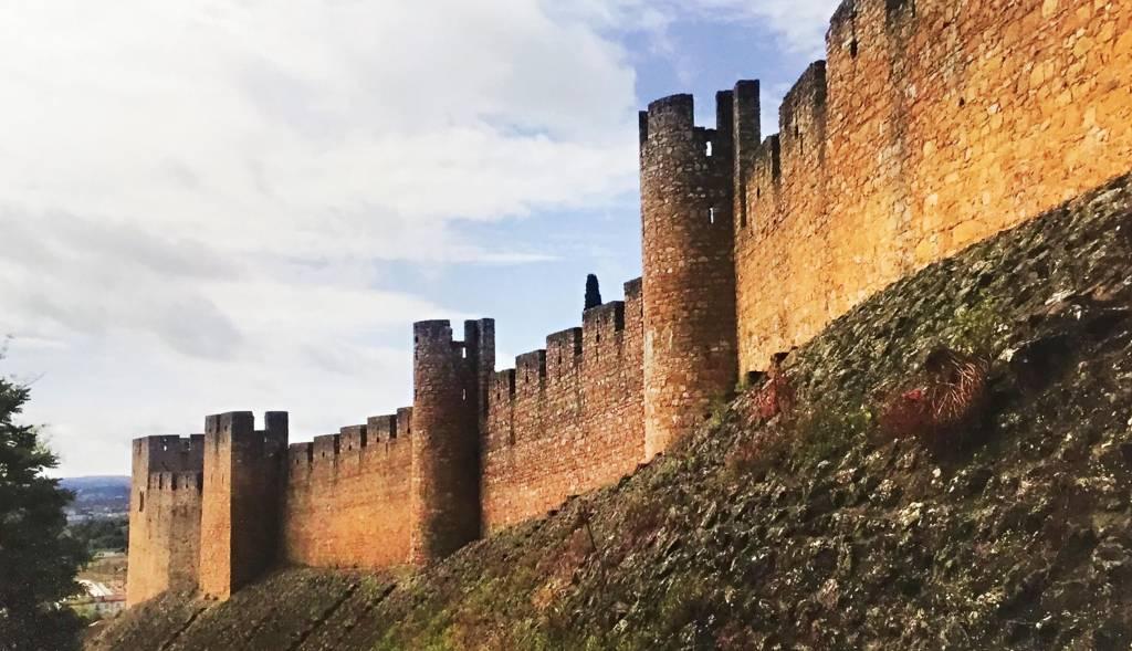 Em cima de uma colina, o muro grosso de uma fortificação medieval se ergue, pontuado por torres de observação.