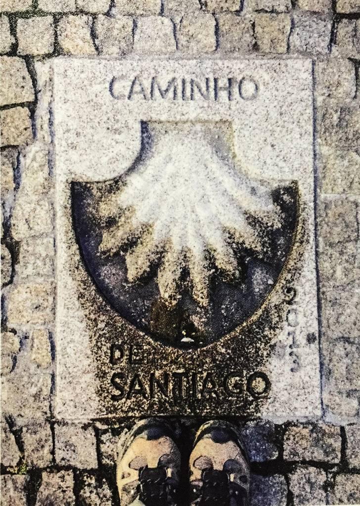 """Uma concha esculpida no chão, com a palavra """"Caminho"""" acima e """"de Santiago"""" abaixo. Em frente à concha estão duas botas, com os bicos apontando em sua direção."""