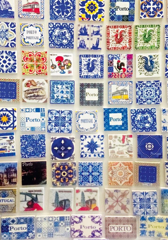 """Um mosaico de ímãs com variadas figuras e dizeres. As mais recorrentes são galos e as palavras """"Porto"""" e """"Portugal"""""""