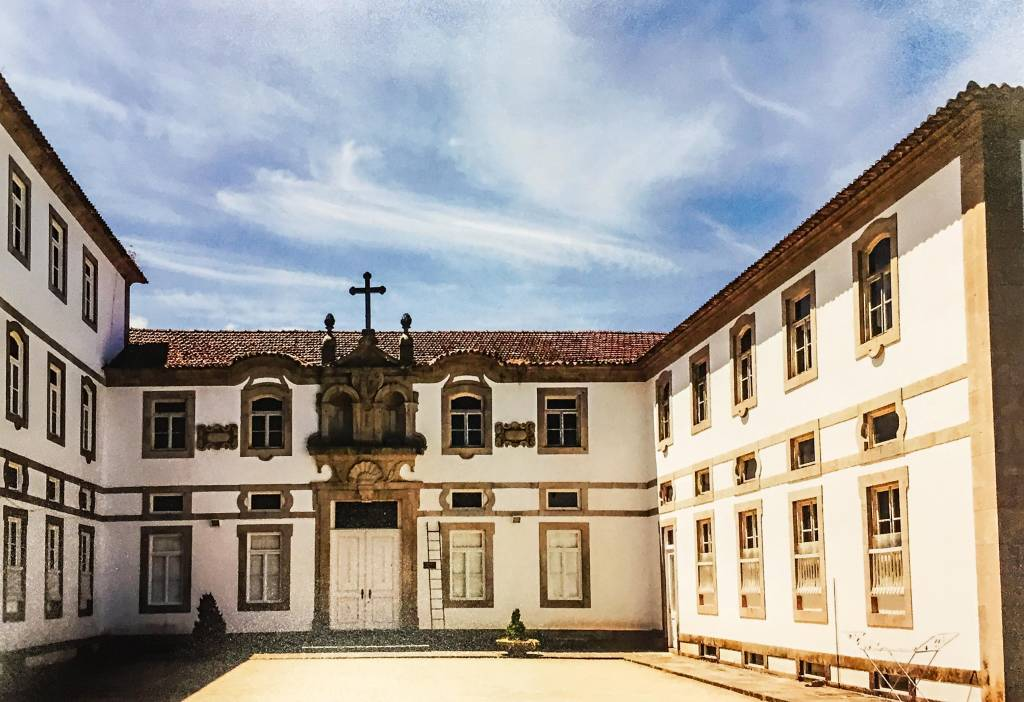 Pátio de um mosteiro de dois andares, vazio. Há uma porta dupla na entrada principal e uma cruz acima dela.