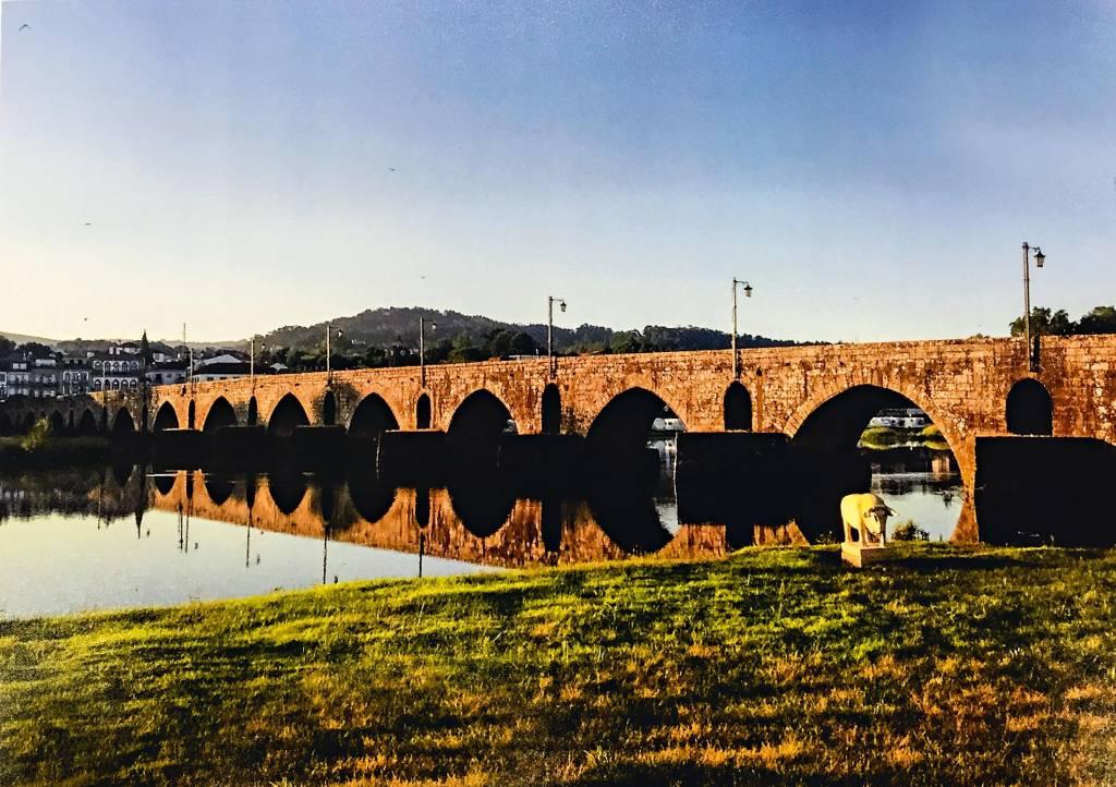 Dividindo a imagem em dois, a ponte de Lima, formada por diversos arcos com bases submersas, parece se aproximar do leitor graças ao ângulo lateral de fotografia. Do lado de cá, grama; do lado de lá, alguns prédios antigos.