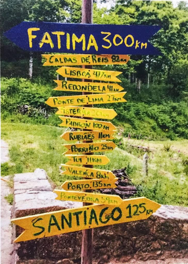 """!4 placas em forma de seta, acopladas a um pau vertical, apontam para diversas localizações. Os nomes das cidades estão escritos à mão, entre eles """"Santiago 125km"""", para a direita e """"Fatima 300km"""" para a esquerda."""