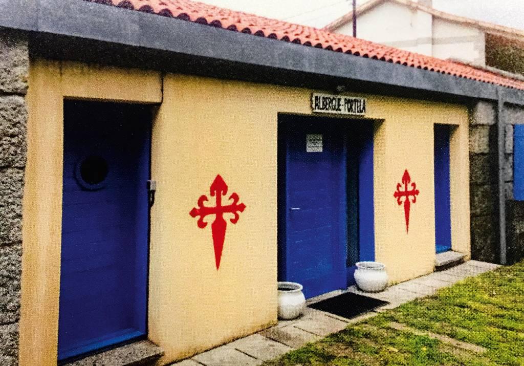 """Três portas vistas de um ângulo lateral. Sobre a porta central, uma placa com os dizeres """"Albergue-Portela"""" está posicionada, e há dois brasões pintados nos muros entre as portas."""
