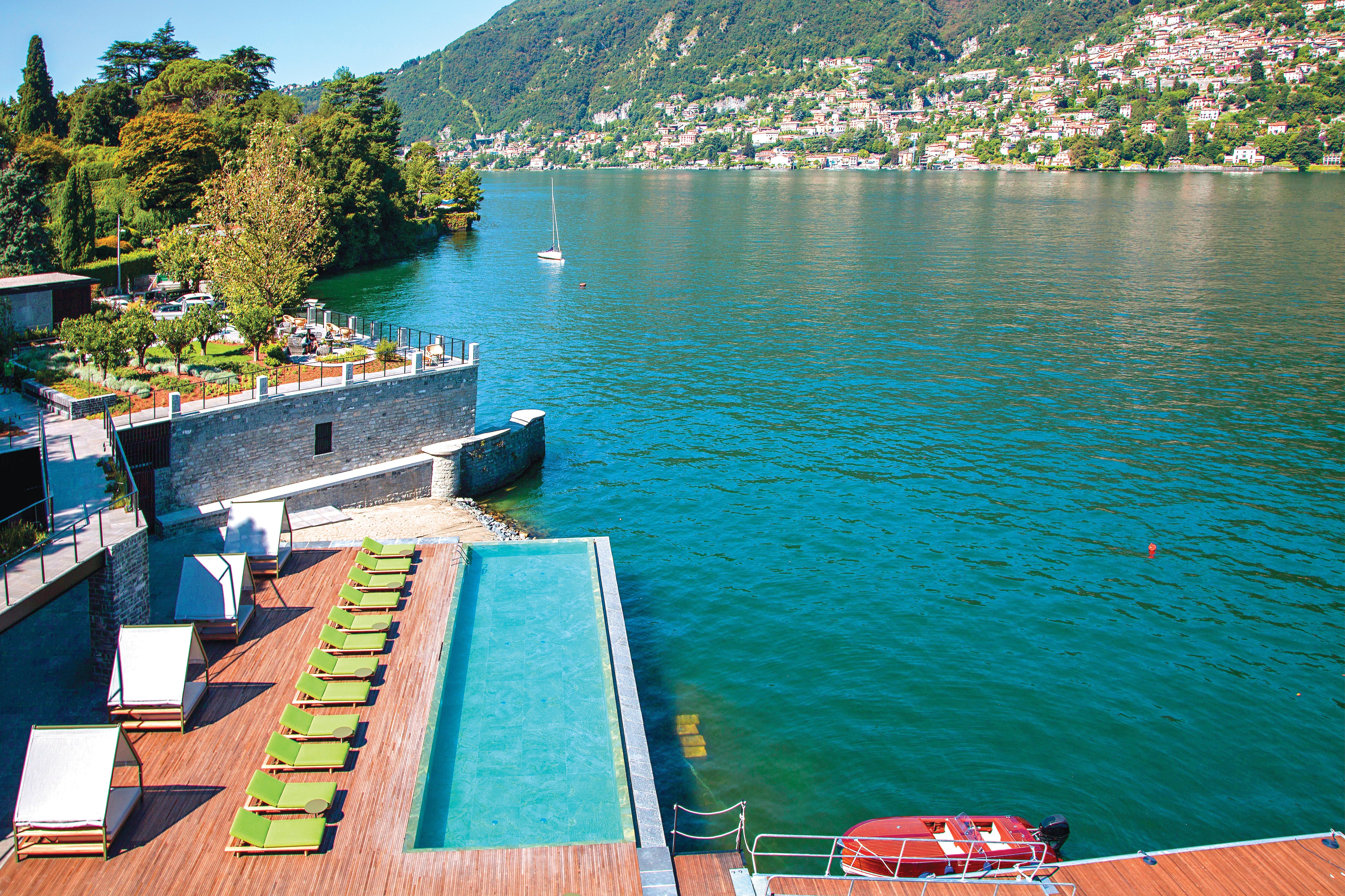 Panorâmica de parte do Lago Como. Em primeiro plano e à beira d'água, cadeiras reclináveis e a piscina compõem o limite do Il Sereno Hotel. Ao fundo, casinhas amontoam-se sob os pés das montanhas