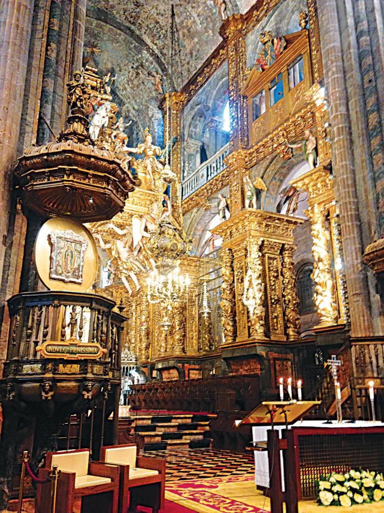 Interior de uma catedral, com tetos altos, pisos de ladrilho de diferentes padrões e grupos de pequenas colunas suportando a estrutura, assim como pinturas e estátuas de santos e madonas, grande parte em ouro.
