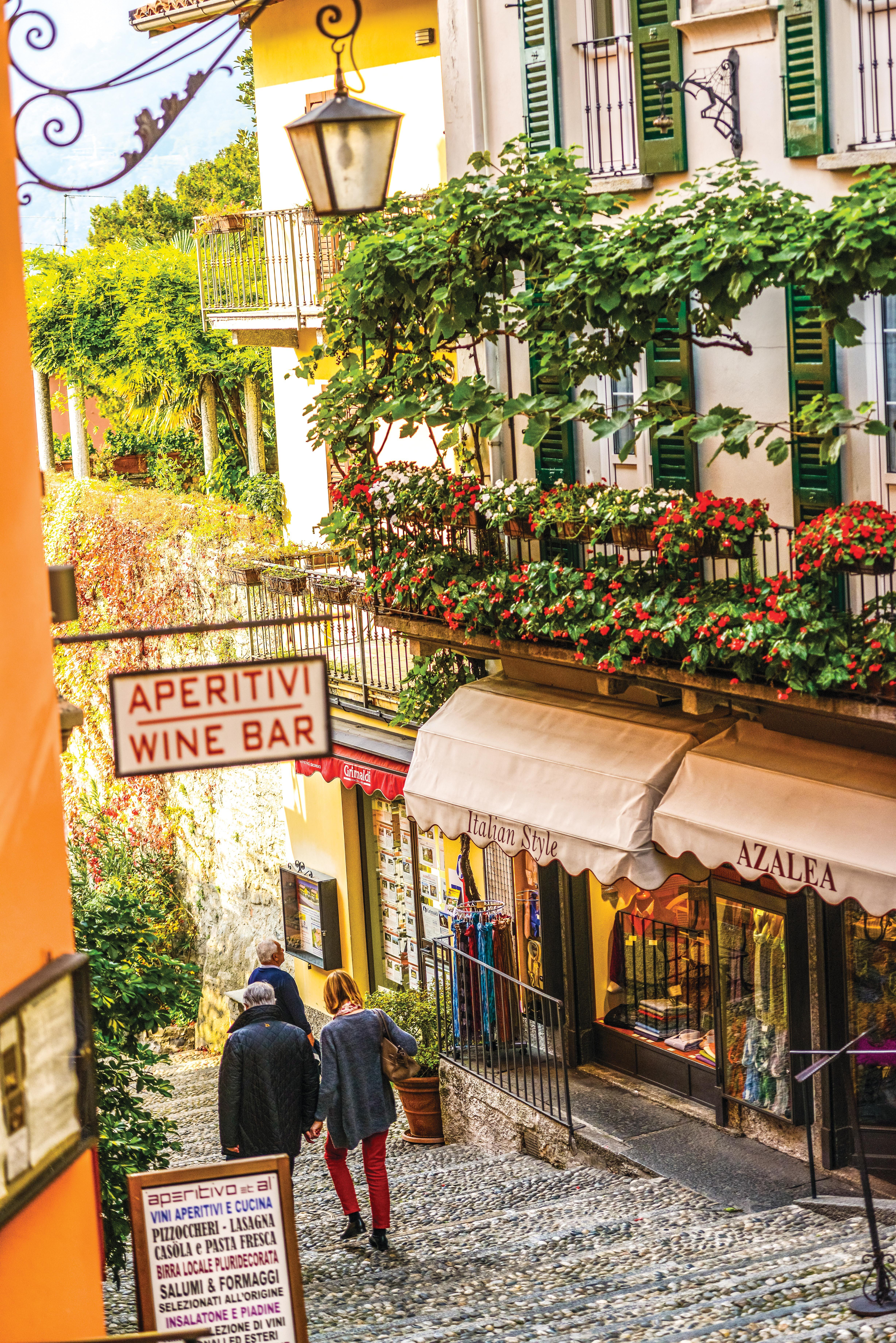 """Um casal desce as escadarias de pedra de uma estreita ladeira. Os prédios que a ladeiam são altos e charmosos, com lojinhas, varandinhas cheias de flores e lâmpadas de rua antigas. Do lado esquerdo, uma placa indica: """"Aperitivi Wine Bar"""""""