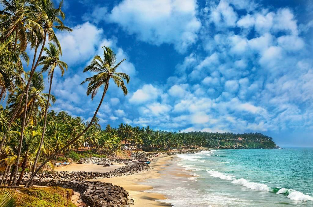 praia quase vazia de sinais humanos embaixo de um céu sem nuvens. Não há muita areia e os coqueiros existem em abundância