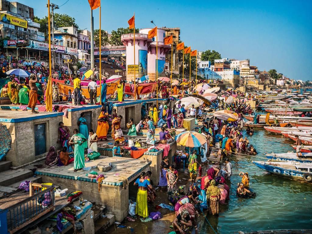 Pioneiros em Dashashwamedh Gha, na beira do Rio Ganges, travam comércio e conversas nos Ghats. O fluxo de pessoas e mercadorias é intenso, vindo da terra ou do mar, por meio de barcos.