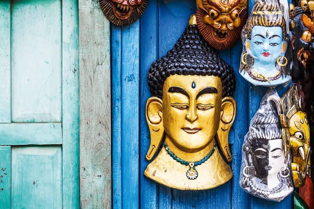 Contra uma estrutura de madeira estão penduradas máscaras de deuses indianos, com penteados altos e muitos brincos e colares