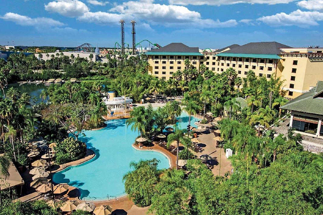 Piscinas, coqueiros, guarda-sóis e prédios do complexo do resort. Ao fundo, é possível avistar montanhas-russas