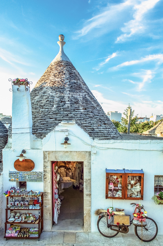 Loja de souvenirs dentro de uma casa em estilo trullo. Do lado de fora, à esquerda da porta, uma prateleira com vários objetos e, à direita, uma bicicleta encostada na parede