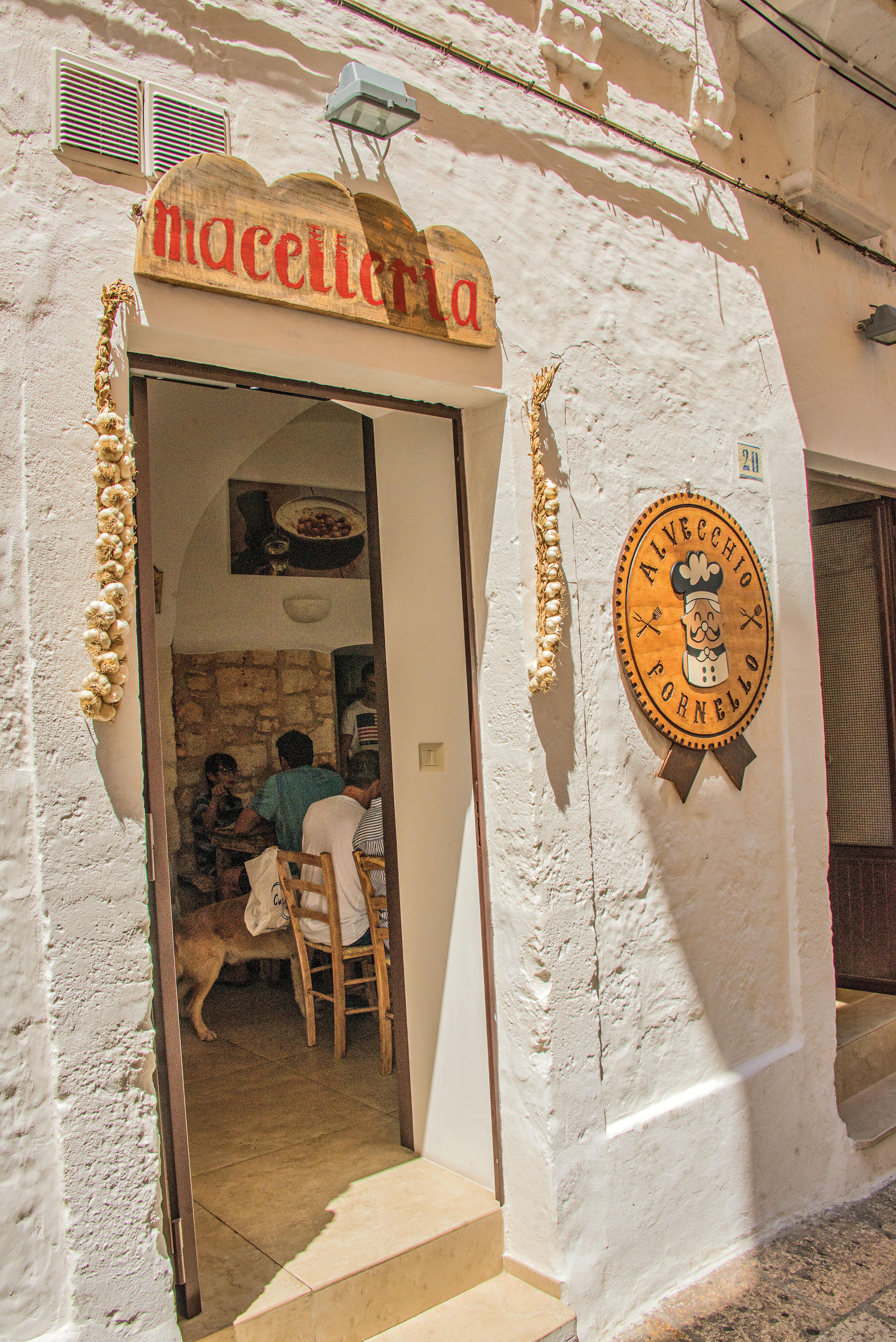 Alta parede branca, com uma porta em que os batentes estão decorados com correntes de alho. Dentro, é possível ver várias meses e cadeiras com clientes consumindo alimentos