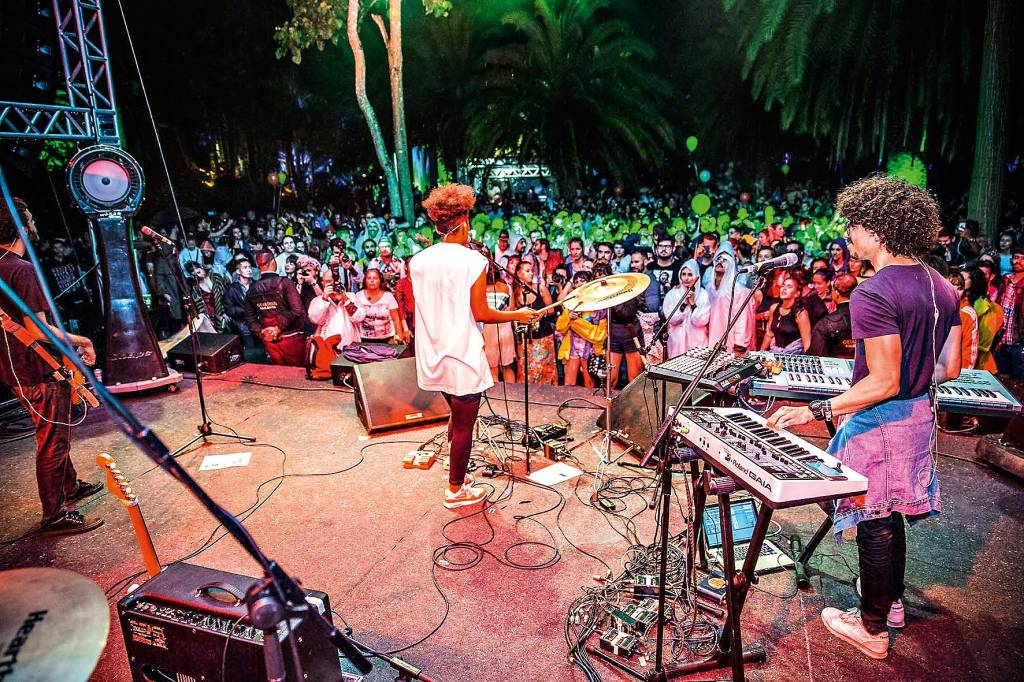 Vista de cima do palco de um show de música, com uma banda de estilo alternativo e uma multidão de espectadores igualmente vestidos.