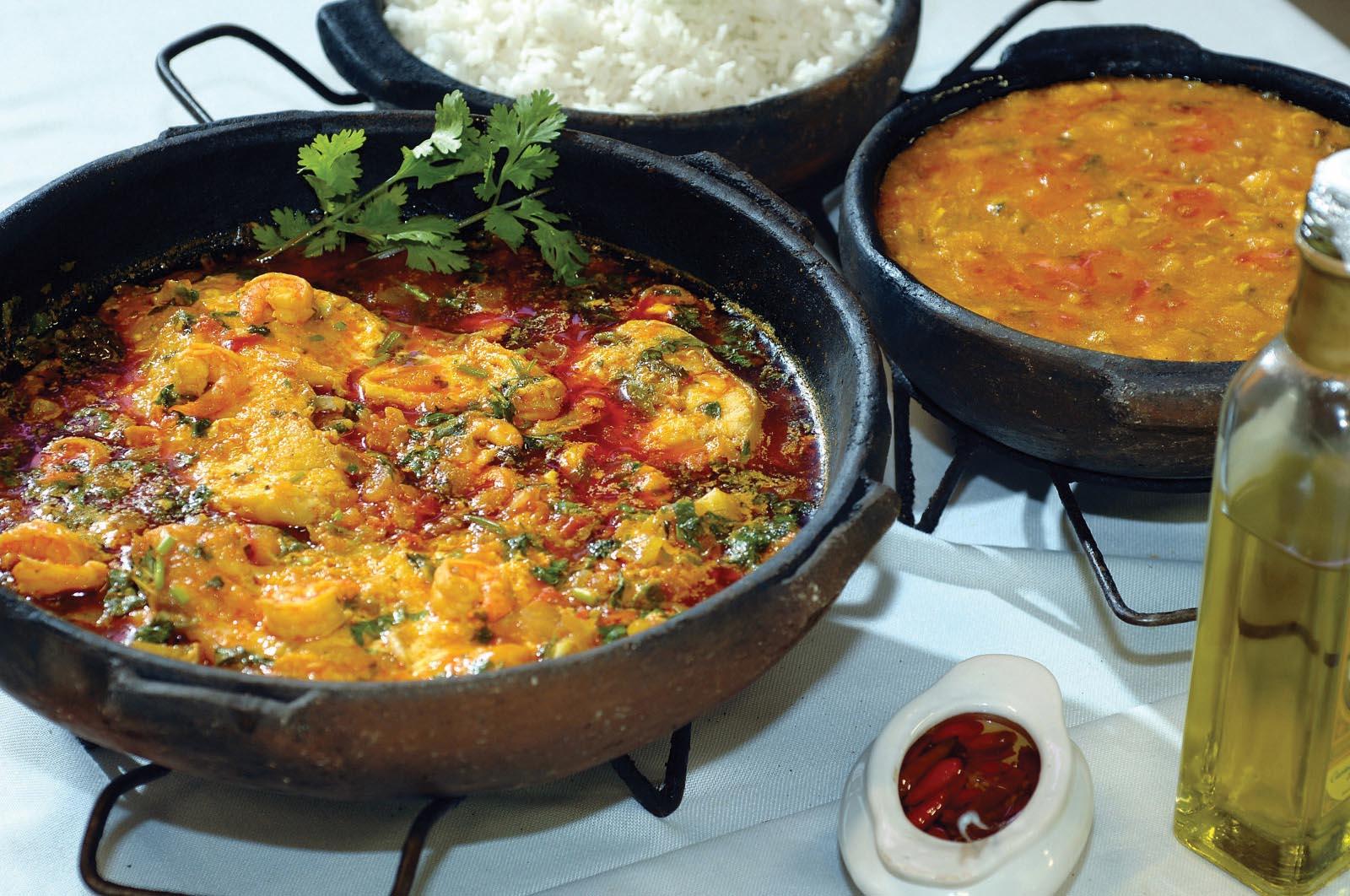 Moqueca dentro de um panela de barro, ao lado de outras que servem arroz e molho de camarão. À esquerda, azeite e um potinho com pimenta capixaba