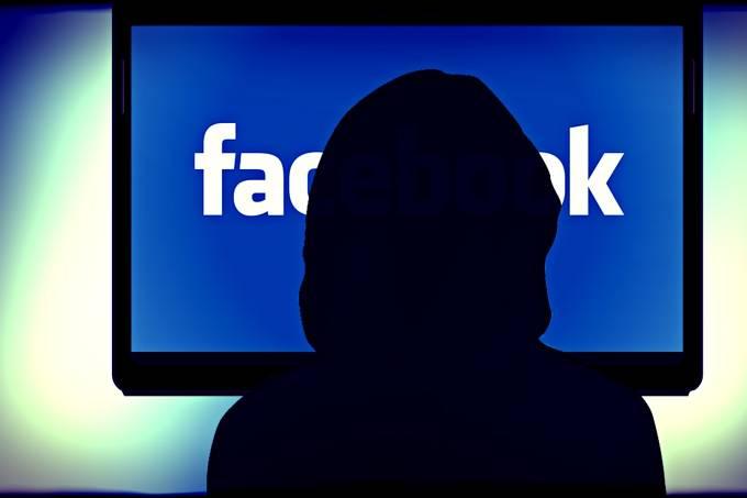 Mulher em frente a tela de computador com o logo do Facebook