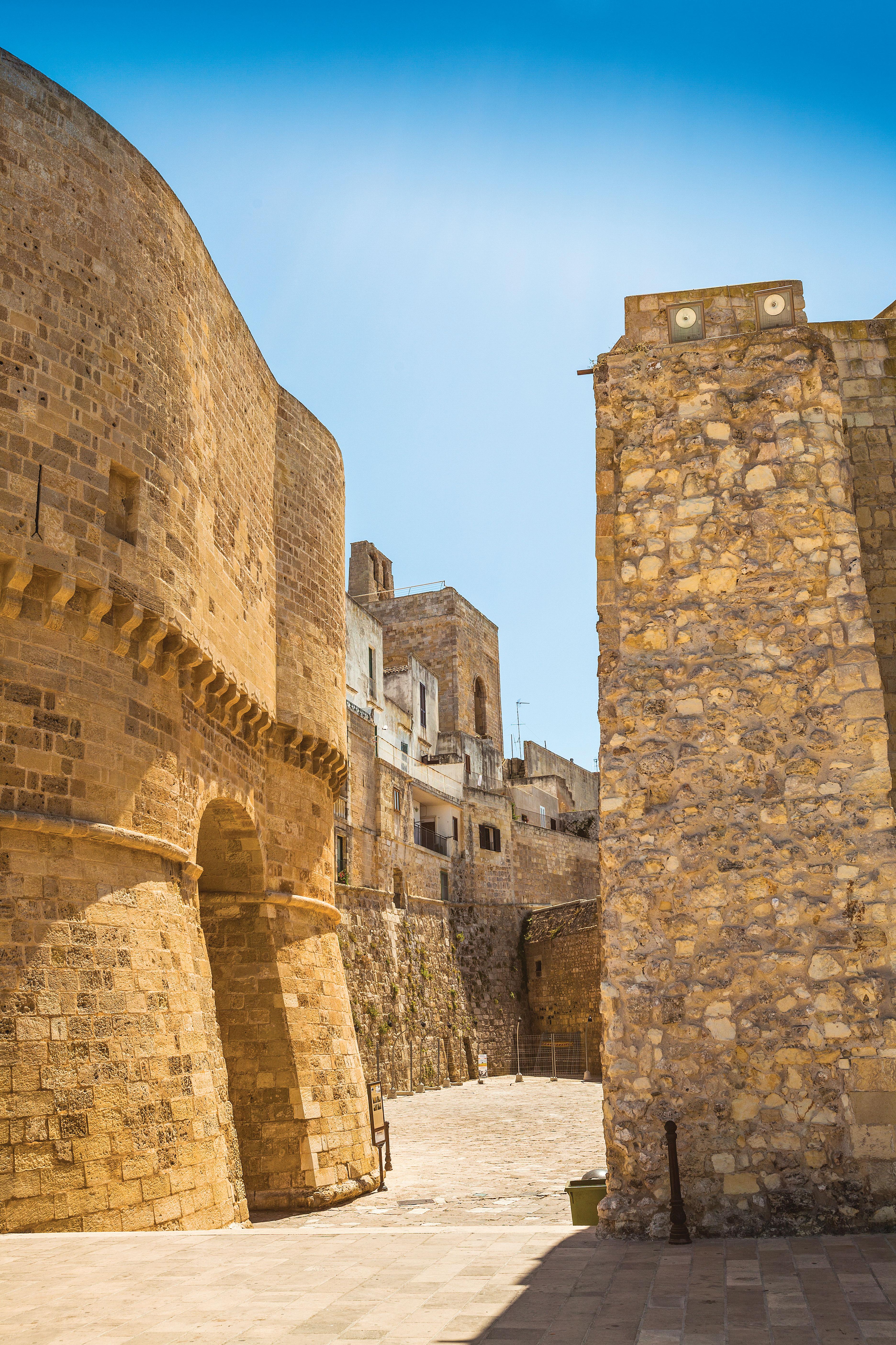 Um beco com altas paredes de tijolos, as quais formam uma seção da muralha de Gallipoli