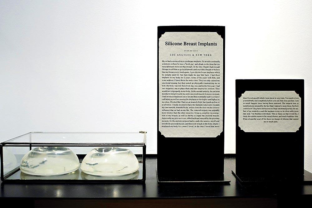 Uma caixa de vidro expõe duas bolsas de silicone. Ao lado, dois totens exibem uma explicação sobre a obra