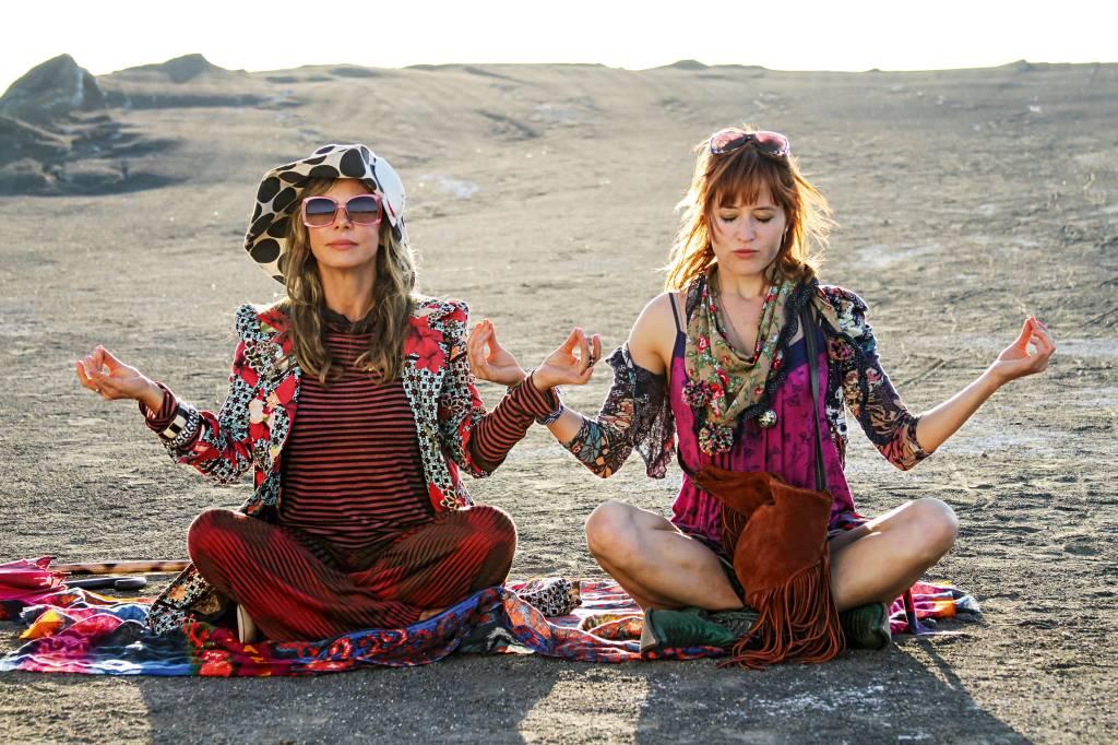 Duas mulheres, vestidas com roupas extravagantes e muitos acessórios, sentam lado a lado, com as mãos levantadas na altura dos ombros em sinal de meditação