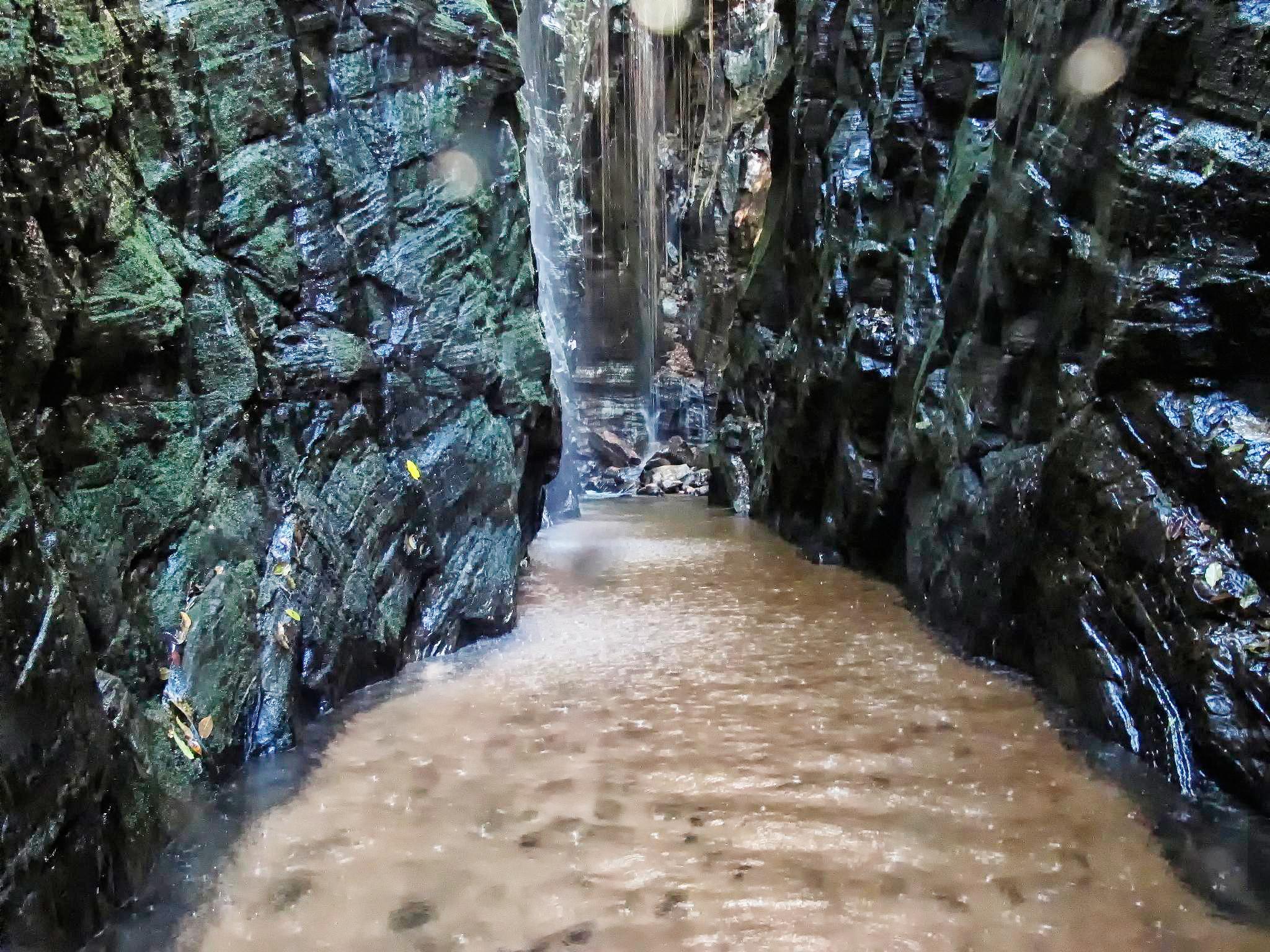 Pedra Caída - cachoeira no meio de um cânion de pedras escuras, com corredor coberto de água até os joelhos, na Chapada das Mesas, Maranhão