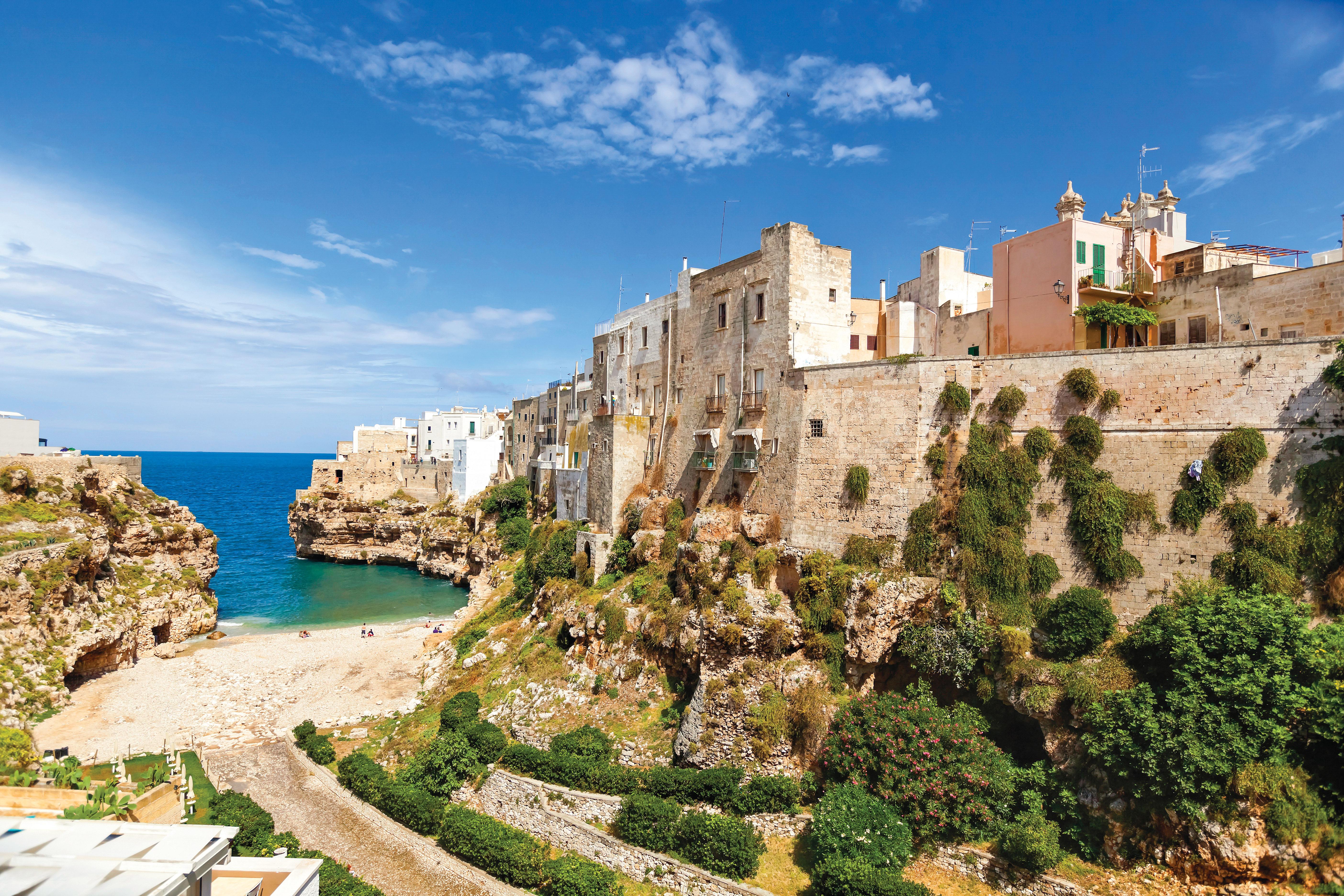Casas e um grande e alto muro, cercado de plantas, à beira de uma praia e com vista para o mar