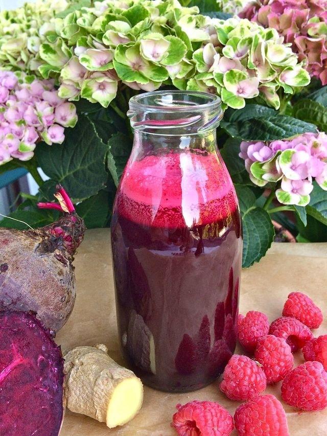 Uma garrafa transparente exibe um suco. Ao lado, pequenas de framboesa, duas beterrabas e um pedaço de gengibre. Flores ocupam o plano de fundo