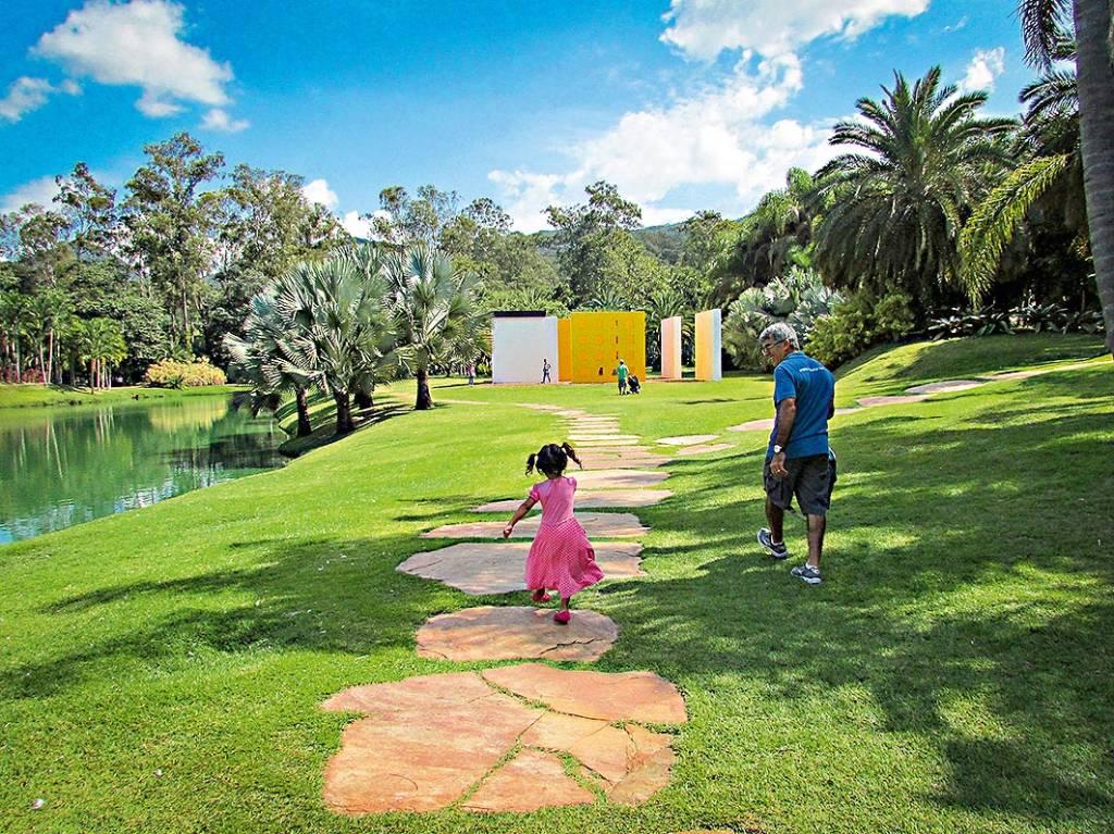 Uma menina anda de forma alegre por um caminho de pedras soterradas, com um homem de cabelo grisalho ao lado e coqueiros e outras árvores em volta. O caminho leva a um grupo de paredes em meio à natureza