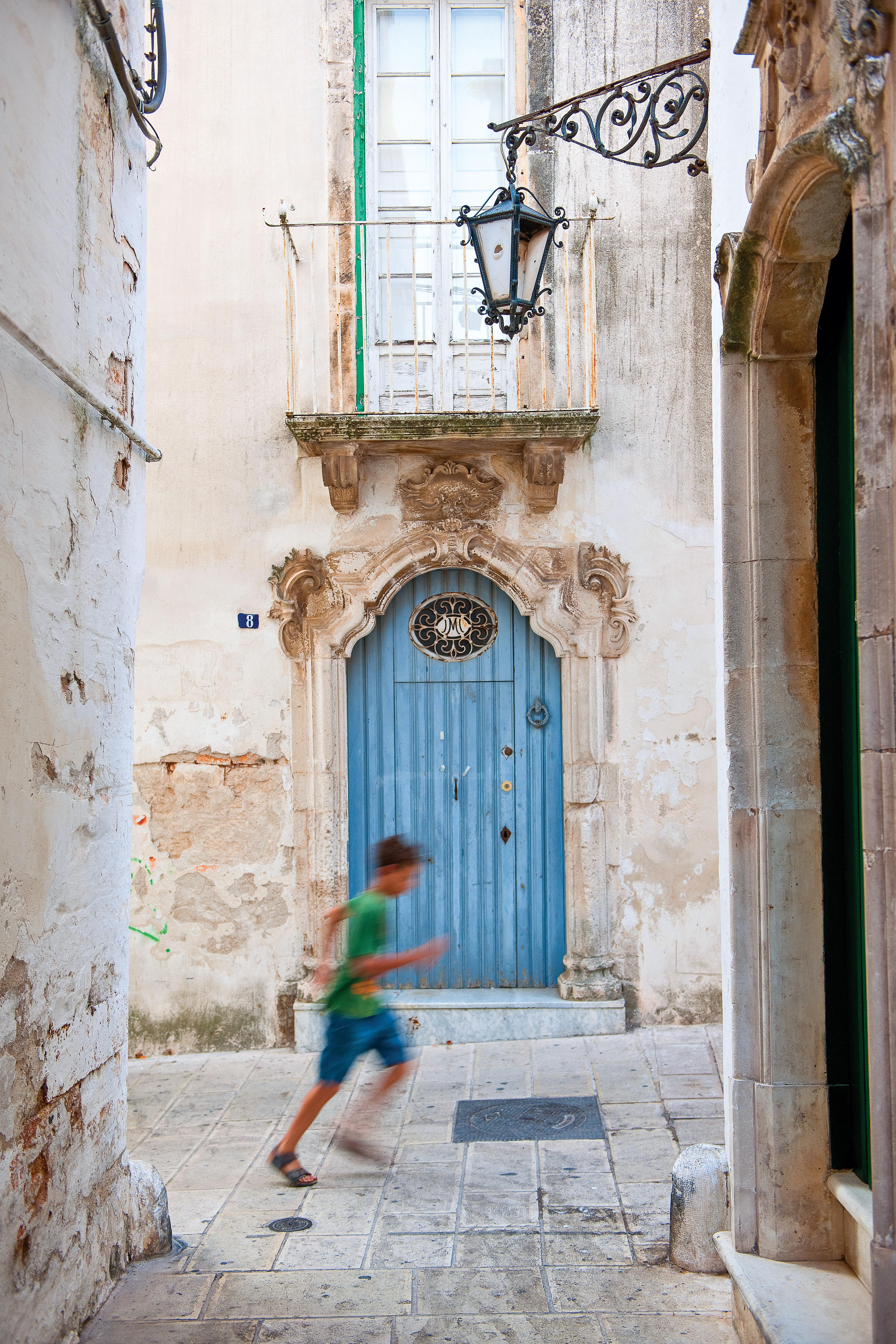 Uma rua com uma grande e ricamente decorada porta. Um menino pequeno corre em frente ao lugar