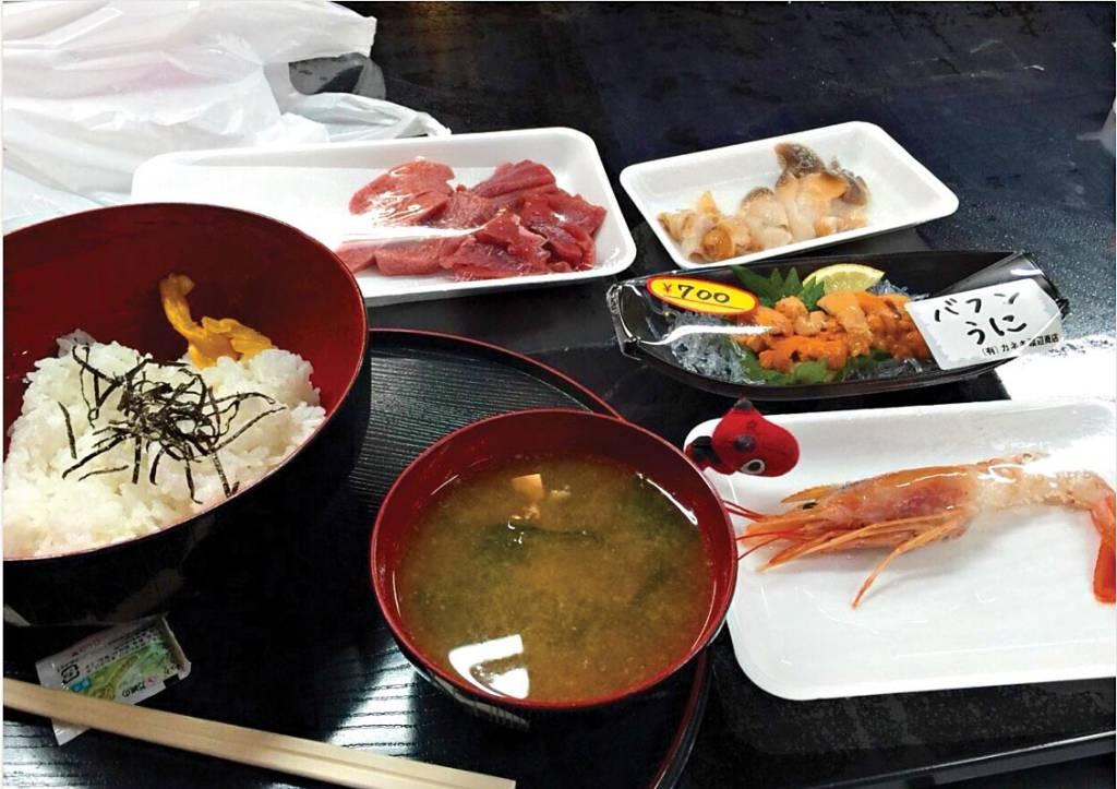 Tigelas e bandejas de comida típica japonesa (arroz, vegetais, miso, cogumelos e camarão) sobre uma mesa