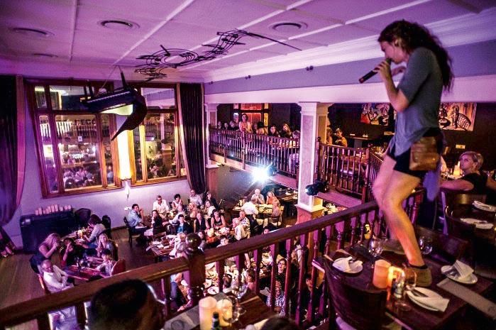 Um cantora está em cima de uma mesa, no segundo andar de um restaurante, se apresentando para a plateia de clientes do restaurante